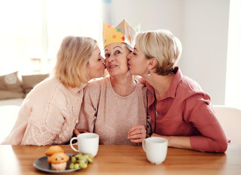 Une m?re sup?rieure avec deux filles adultes s'asseyant ? la table ? la maison, ayant l'amusement photographie stock libre de droits