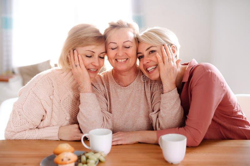 Une m?re sup?rieure avec deux filles adultes s'asseyant ? la table ? la maison photo stock