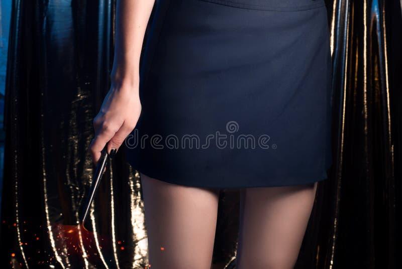 Une magicienne d'adolescente avec une baguette magique magique, une fille dans une jupe, les jambes minces, photo stock