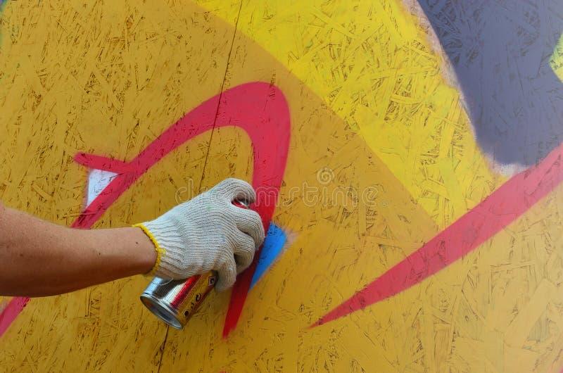Une main avec une boîte de jet qui dessine un nouveau graffiti sur le mur images libres de droits