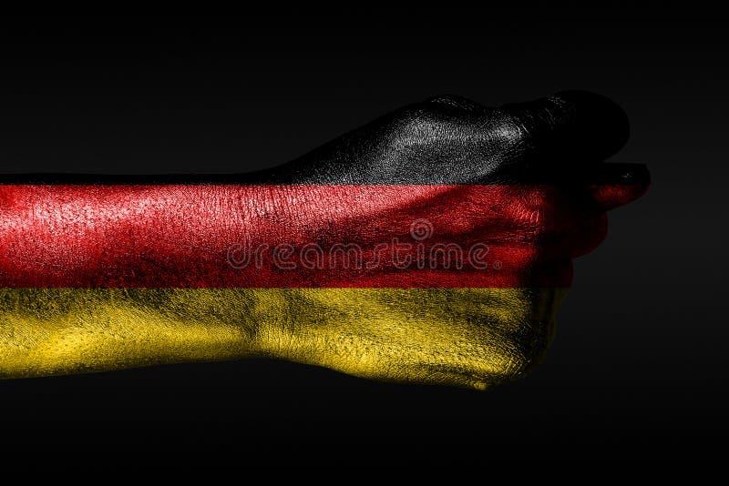 Une main avec un drapeau peint de l'Allemagne montre une figue, un signe d'agression, le d?saccord, un conflit sur un fond fonc? image stock