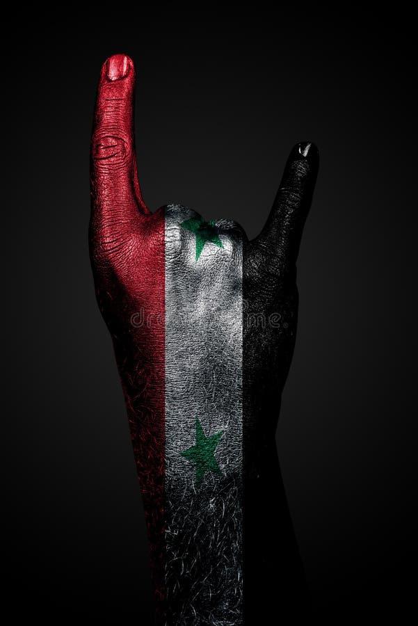 Une main avec un drapeau tir? de la Syrie montre un signe de ch?vre, un symbole de courant principal, le m?tal et la musique rock images stock