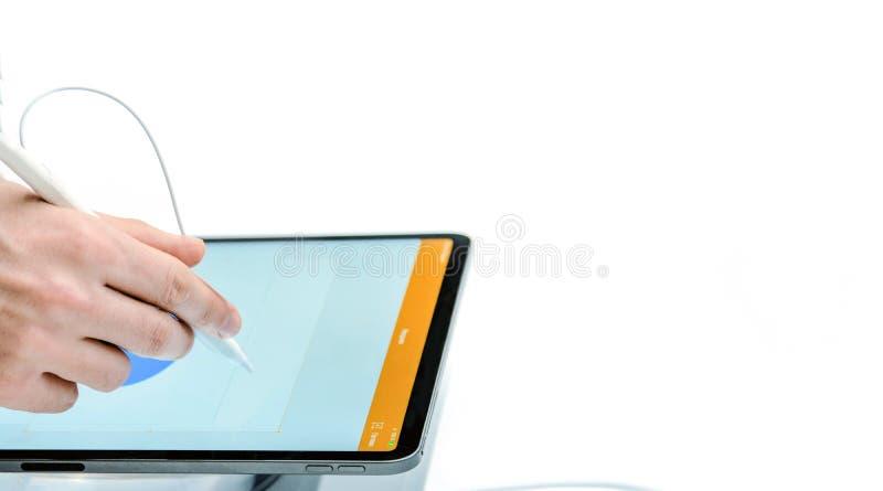 Une main avec un stylet dessine sur un comprimé Technologie numérique Fond d'isolement par blanc Plan rapproché photographie stock