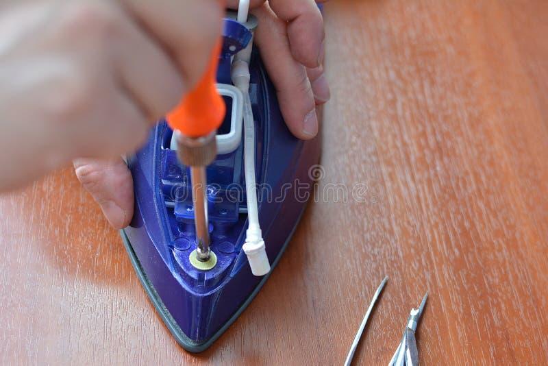 Une main avec un tournevis démantèle le fer photos stock