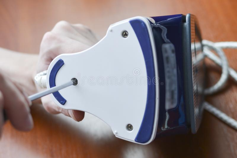 Une main avec un tournevis démantèle le fer images stock