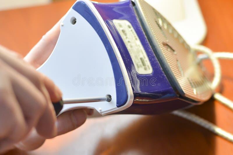 Une main avec un tournevis démantèle le fer photographie stock