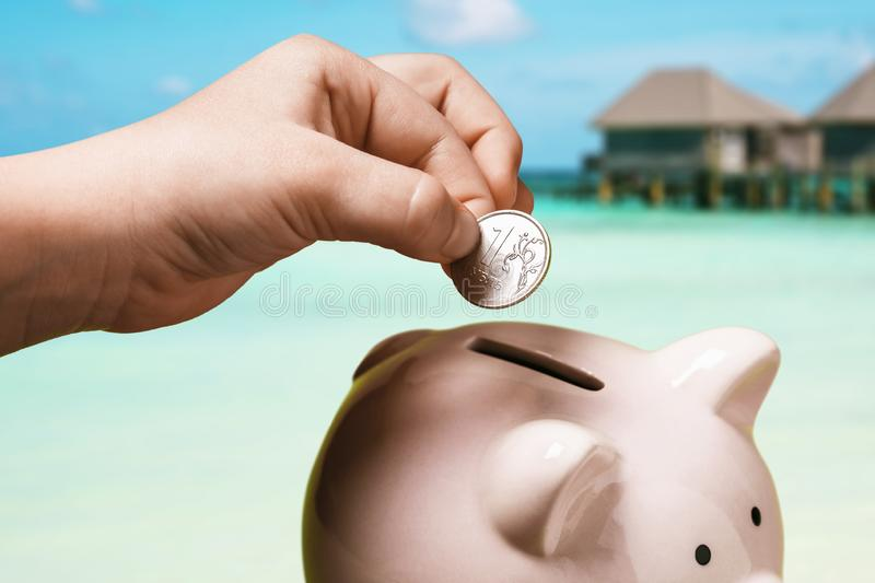 Une main d'enfant met un rouble dans une tirelire Combien d'argent faut-il pour des vacances en mer pour les touristes russes ? photos libres de droits