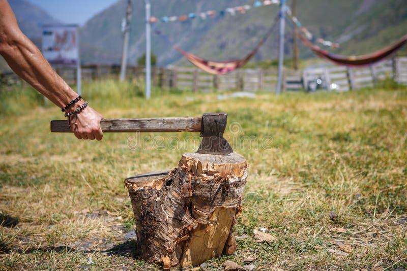 Une main d'homme fort avec une hache coupant le bois à un camping dans une région montagneuse de la Géorgie photographie stock libre de droits