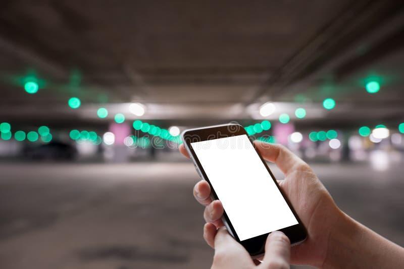 Une main d'homme tenant le dispositif intelligent de téléphone avec le backgr de bokeh de parking images libres de droits