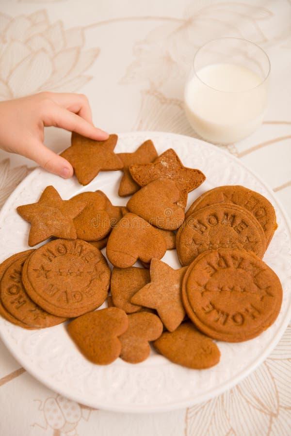 Une main d'un enfant prenant les biscuits à la maison nouvellement fabriqués de vacances dans les formes des débuts, des coeurs e images libres de droits