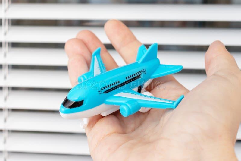 Une main d'un homme d'affaires tenant un avion de jouet - voyage d'affaires et concept de déplacement photographie stock libre de droits