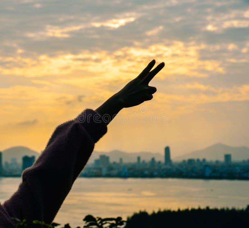 Une main de femme avec le paysage marin de coucher du soleil images libres de droits