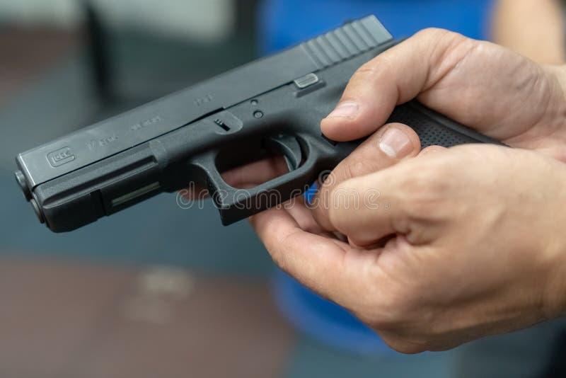 Une main de l'homme pratiquant mettant le feu utilisant un modèle d'arme à feu de Glock au champ de tir Arme à feu de main de glo image libre de droits