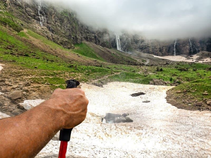 Une main de touristes avant d'aller à une vallée de montagne avec les cascades grandes images stock