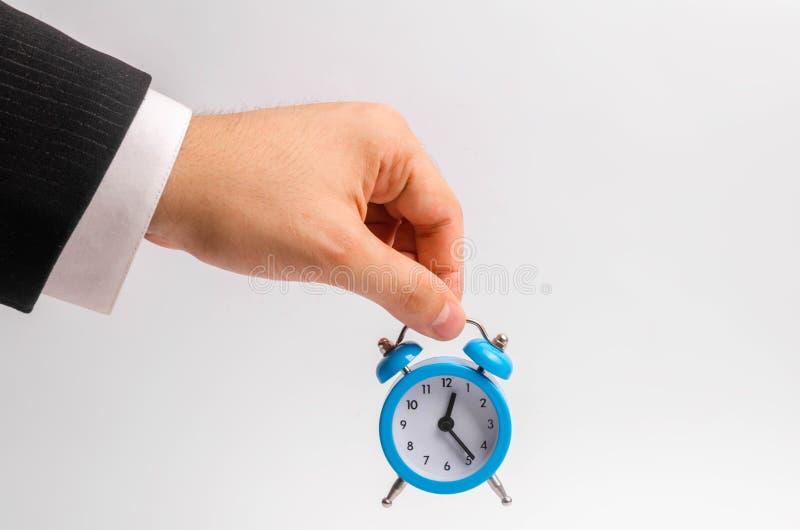 Une main du ` s d'homme d'affaires tient un réveil bleu sur un fond blanc Le concept de l'écoulement du temps, temps à l'action S photos libres de droits