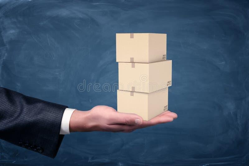 Une main du ` s d'homme d'affaires tenant un ensemble de petite paume de trois boîtes en carton sur le fond de tableau photo libre de droits