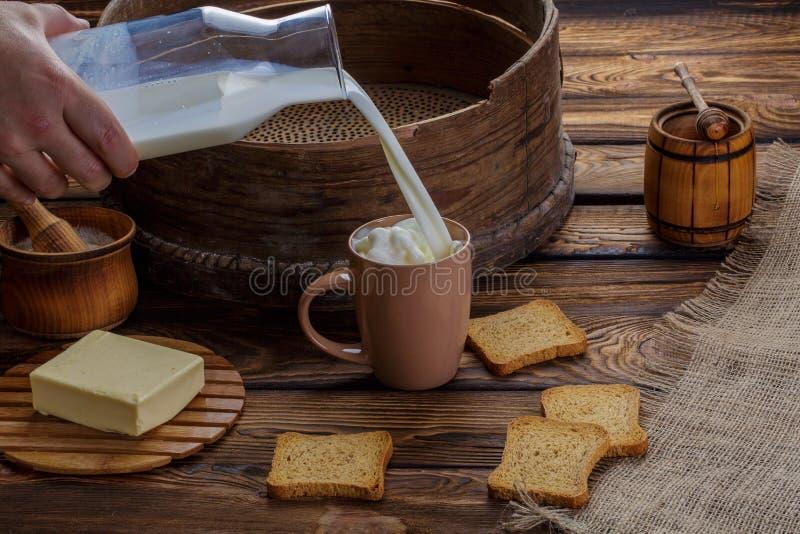 Une main du ` s d'homme verse le lait dans une tasse sur le fond de la toile de jute et d'un fond en bois Autour des biscuits dis image libre de droits