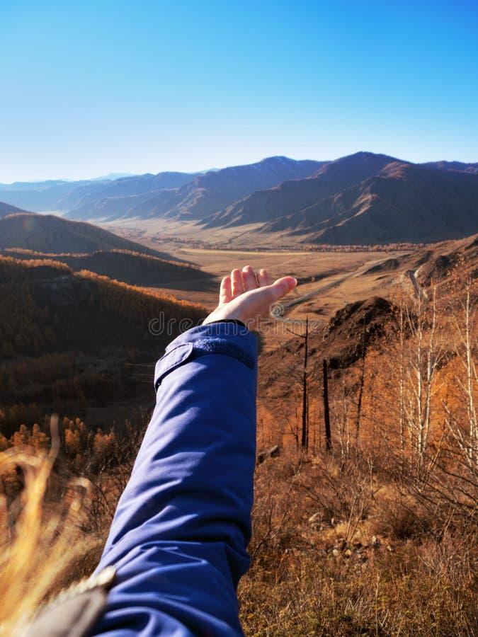 Une main du ` s de femme étirée à la beauté des montagnes photo stock