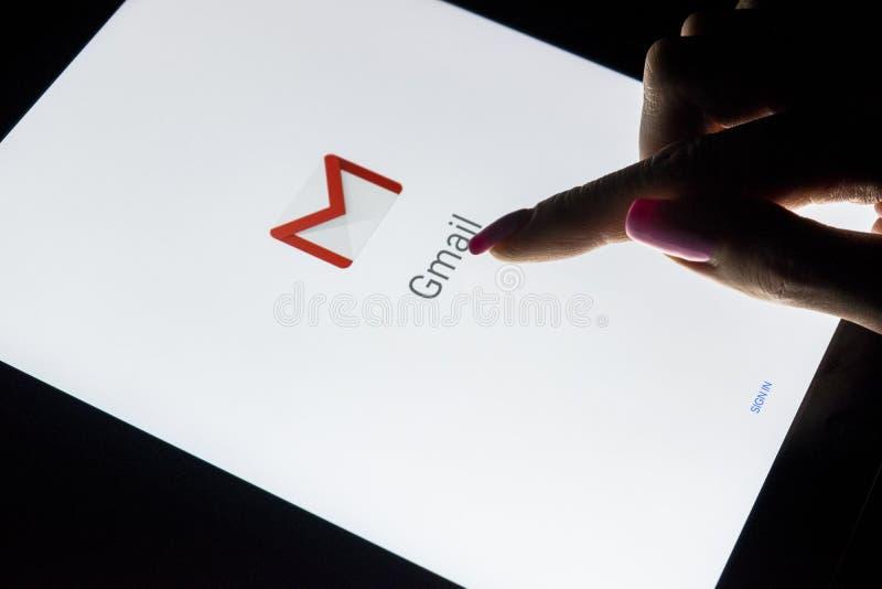 Une main du ` s de femme est écran tactile sur l'iPad de tablette pro la nuit avec l'application ouverte de Google Gmail Gmail es photographie stock libre de droits