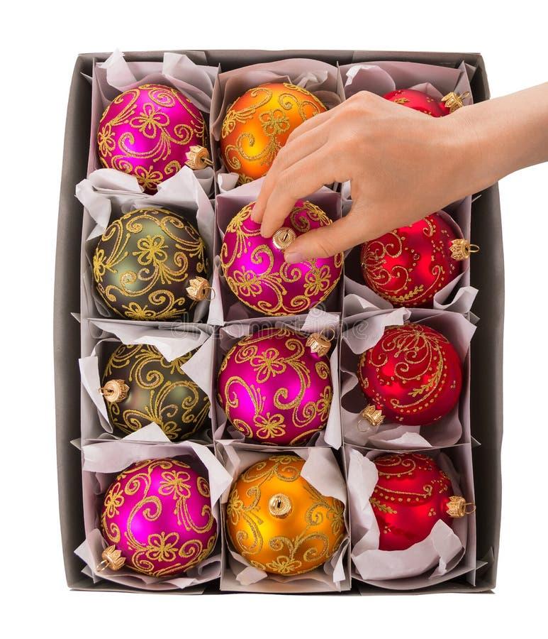 Une main du ` s de femme prend les jouets lumineux et colorés du ` s de nouvelle année images libres de droits