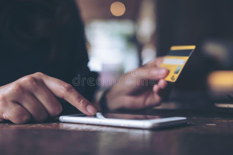 Une main du ` s de femme tenant la carte de crédit et pressant au téléphone portable sur la table en bois dans le bureau photographie stock