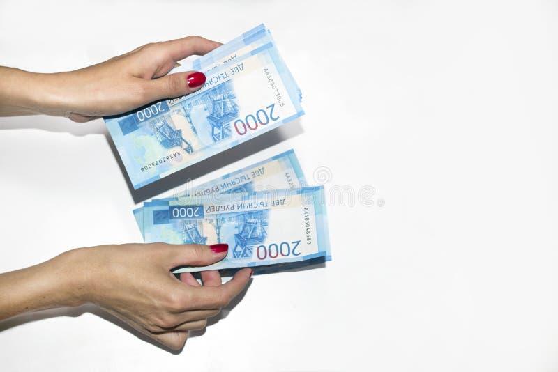 Une main du ` s de femme tient la monnaie fiduciaire Rouble russe photographie stock libre de droits