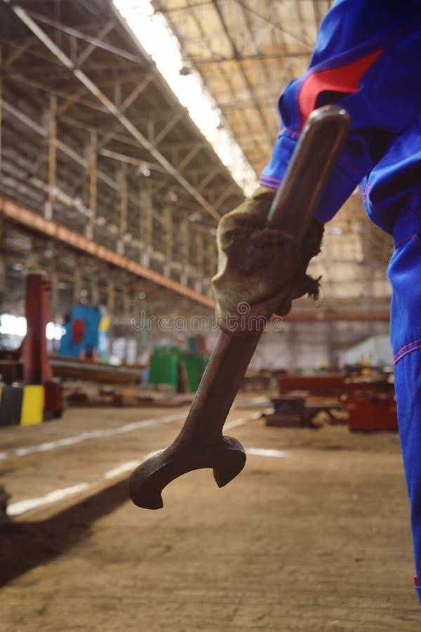 Une main du ` s de travailleur avec une clé énorme photographie stock