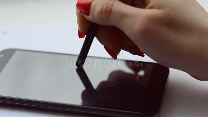 Une main femelle avec la manucure rouge écrit le texte dans une note sur un smartphone clips vidéos