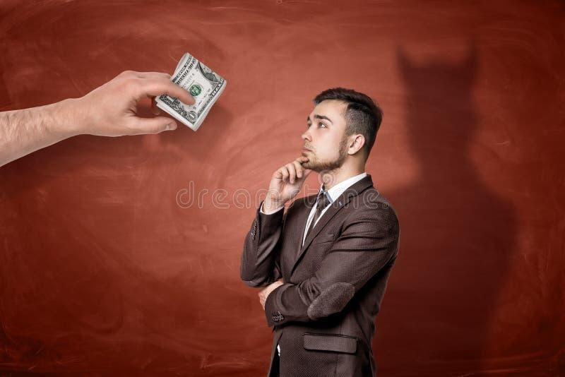 Une main géante avec un rouleau de billets d'un dollar devant un homme d'affaires de pensée qui a moulé une ombre d'un diable image libre de droits