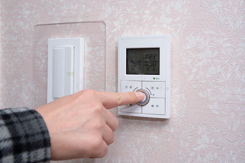 Une main masculine ajustant la température ambiante en hiver photos stock