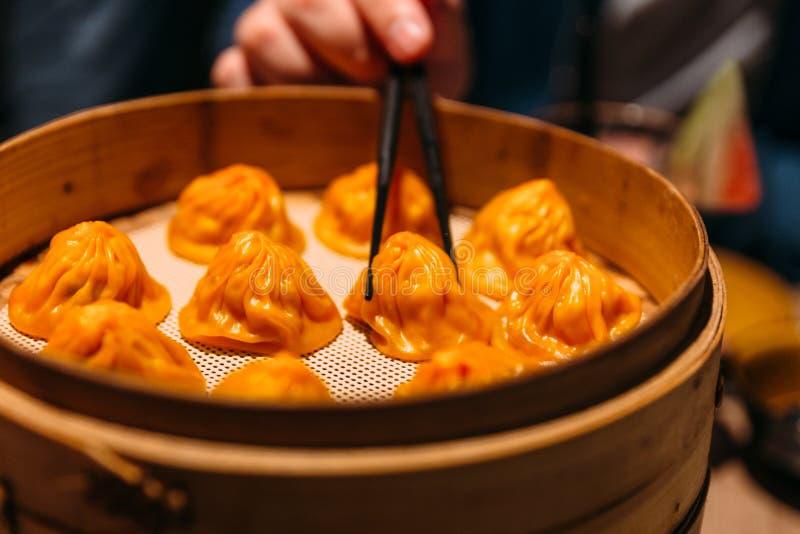 Une main pince la boulette orange de Foie Gras Xiao Long Bao Chinese Soup de couleur avec des baguettes de la flamme en bambou photos libres de droits