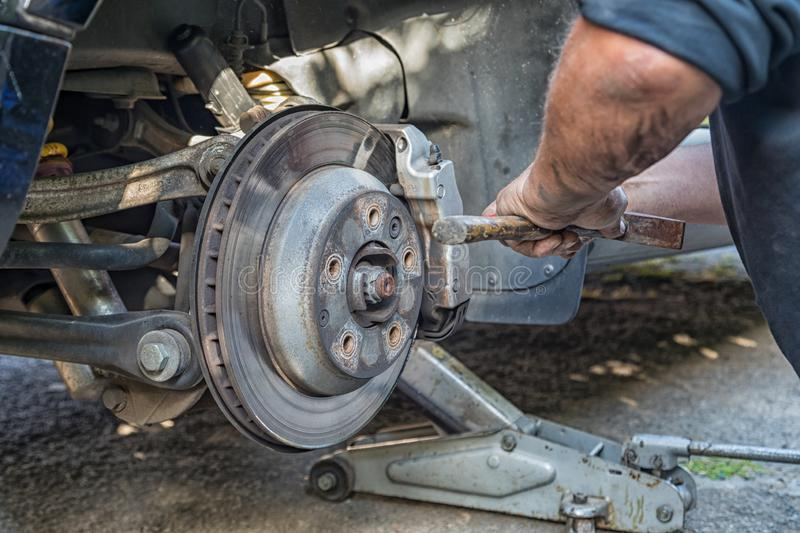 Une main protections de frein changeantes sur une voiture photo stock
