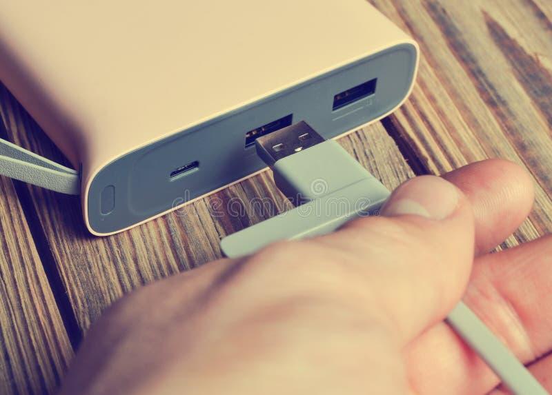 Une main relie un câble d'usb à une banque de puissance photo stock