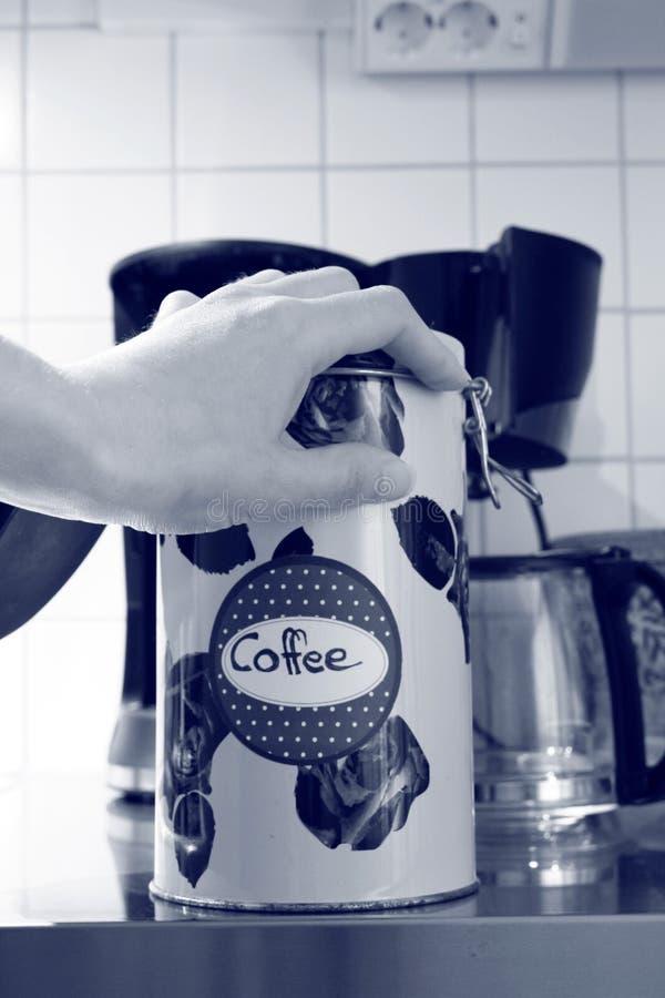 Une main se trouve sur une bo?te en fer blanc de caf? photographie stock libre de droits