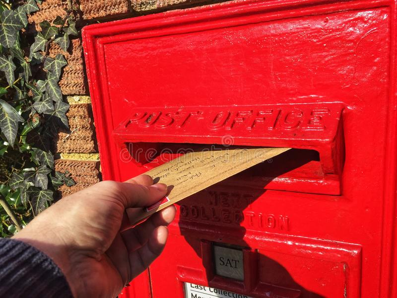 Une main signalant une lettre dans une boîte aux lettres photos libres de droits