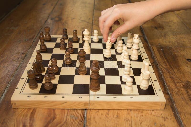 Une main simple jouant des échecs sur un conseil en bois a placé sur certains en bois photographie stock libre de droits
