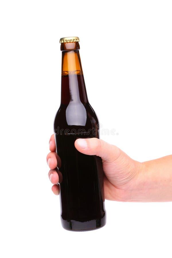 Une main supportant une bouteille à bière brune photographie stock