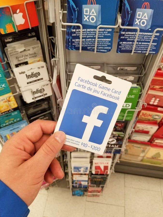 Une main tenant une carte cadeaux de Facebook image libre de droits