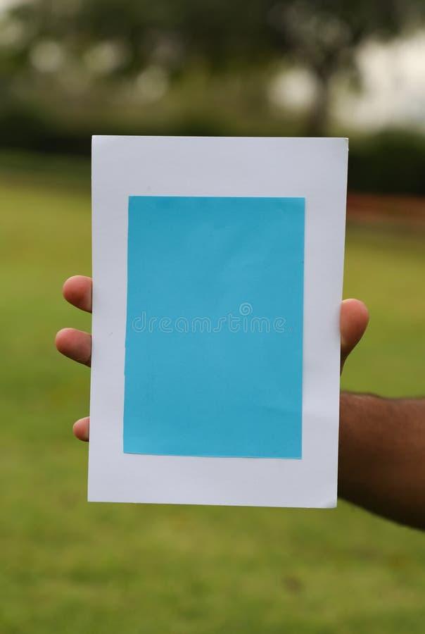 Une main tenant le cadre de tableau avec des feuilles de fruit et de figue dispersant à l'arrière-plan images libres de droits