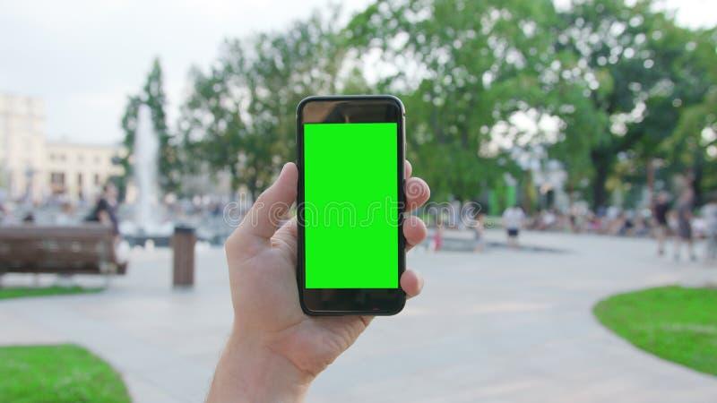 Une main tenant un téléphone avec un écran vert image libre de droits