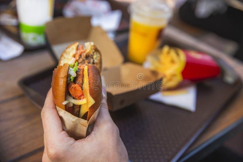Une main tient l'hamburger mordu Plateau avec la nourriture sur le fond image stock