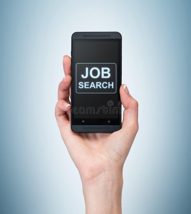 Une main tient un smartphone de fantaisie Mots : 'Recherches d'emploi sur l'écran Un concept du recrutement image libre de droits