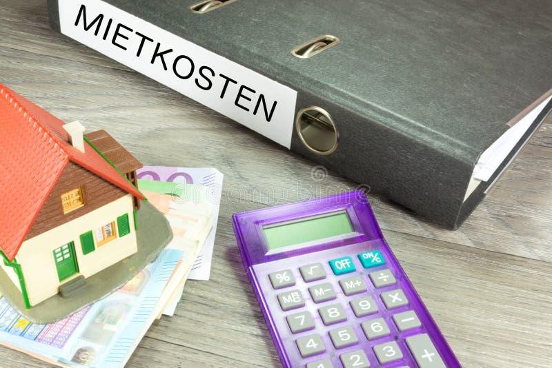 Une maison, de euro factures et un dossier avec les coûts de loyer de mot image stock