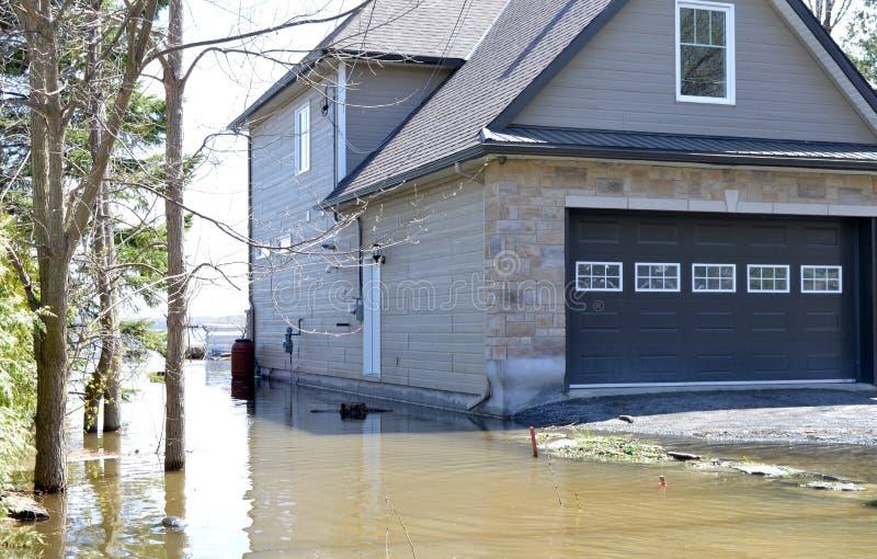 Une maison est menacée par les niveaux d'eaux en hausse de la rivière images libres de droits