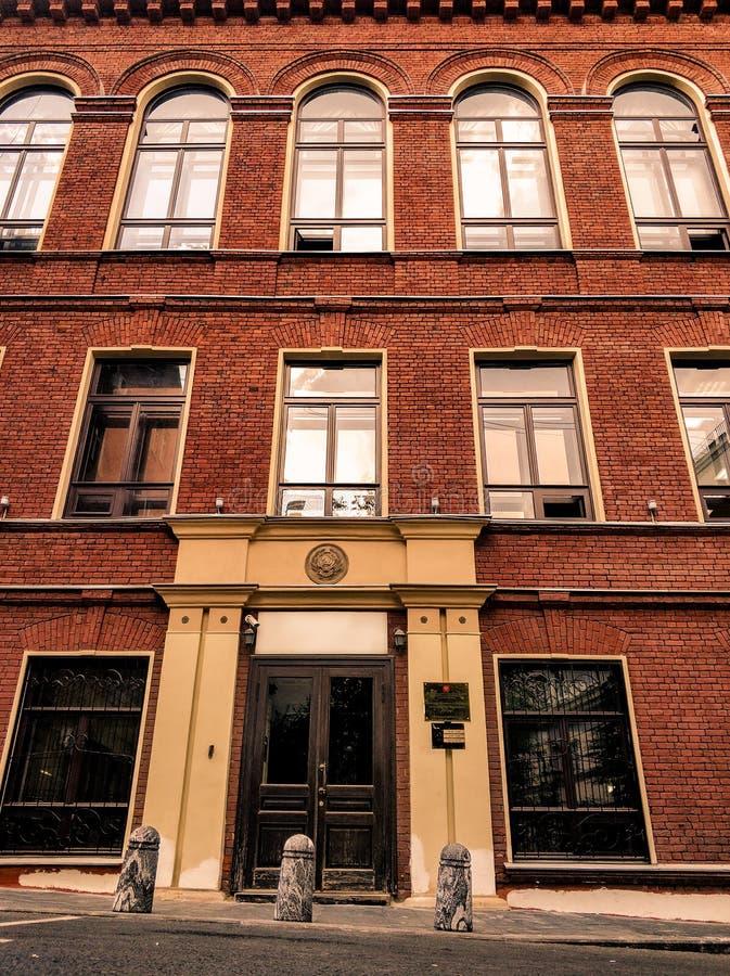 Une maison residental à plusiers étages de brique rouge avec quelques fenêtres sautées photographie stock libre de droits