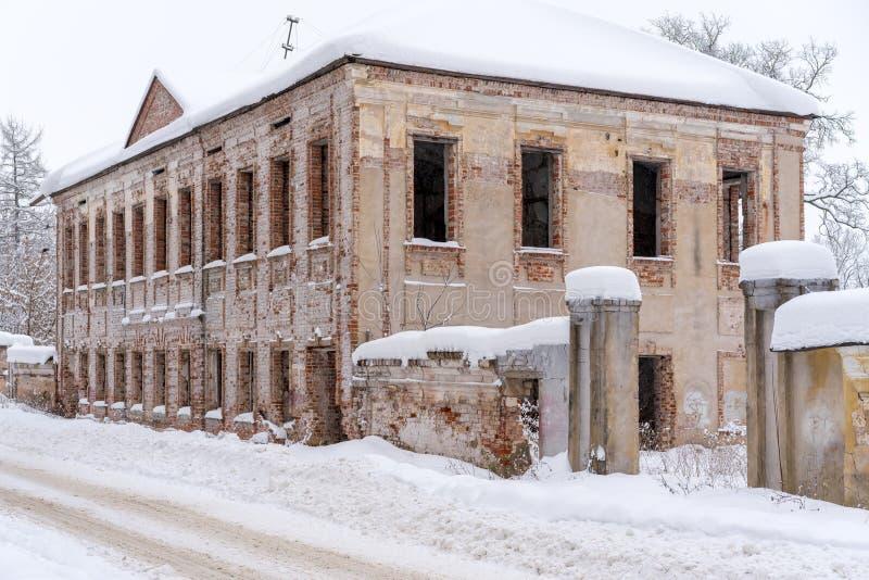 Une maison ruinée deux-racontée de vieille brique dans la rue de la petite ville russe en hiver photos stock