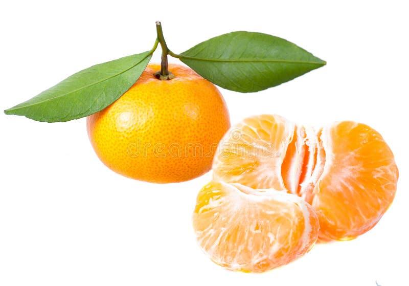 Une mandarine avec des lames et des segments de vert photo stock