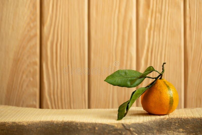 Une mandarine avec les feuilles vertes se trouve sur le conseil en bois sur le fond en bois vertical image libre de droits