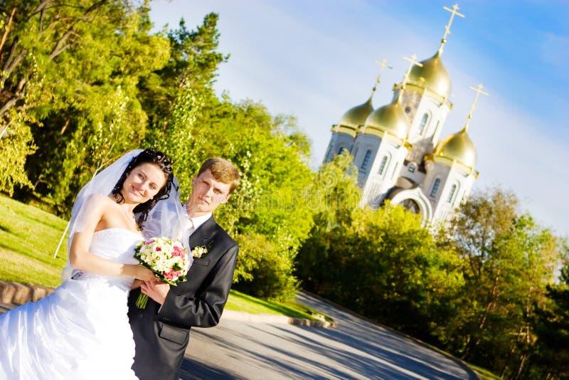Une mariée et un marié près de l'église photos stock