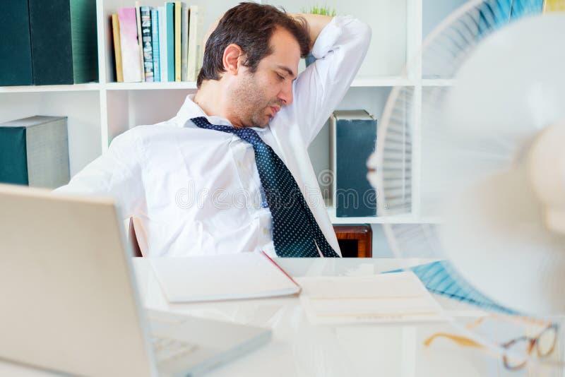 Une mauvaise odeur pour les aisselles d'homme d'affaires au travail photo stock